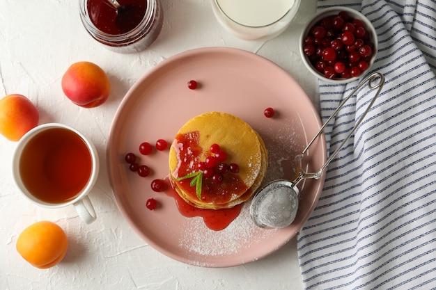 Samenstelling met pannenkoeken met jam en cranberry op witte ruimte Premium Foto