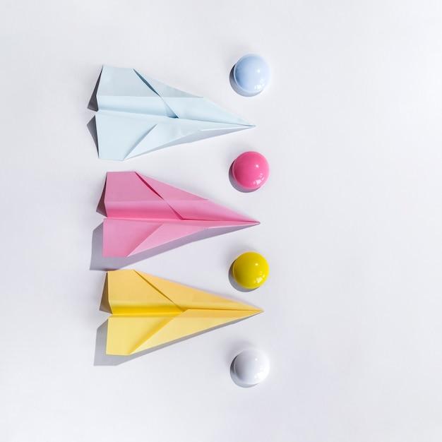 Samenstelling met papieren vliegtuigje op tafel Gratis Foto