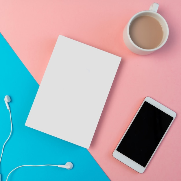 Samenstelling met smartphone, hoofdtelefoon, kladblok en kopje koffie Premium Foto