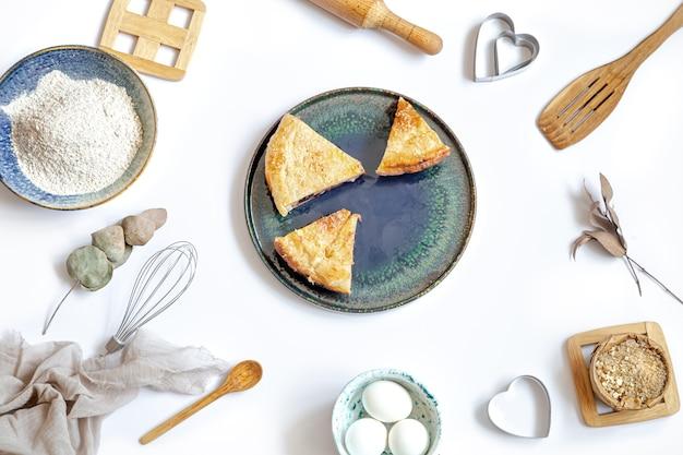 Samenstelling met stukjes taart op een bord en ingrediënten voor het koken en keukenaccessoires op witte tafel. Gratis Foto