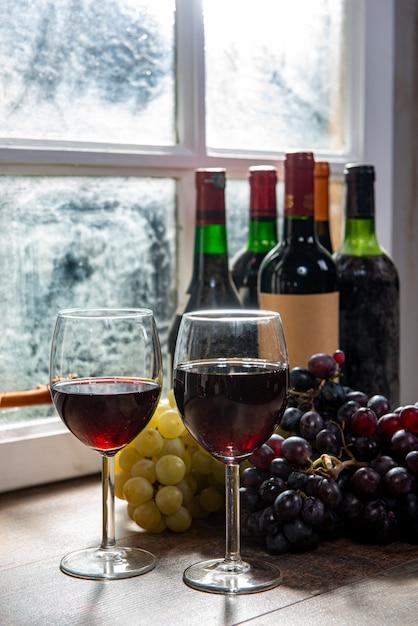Samenstelling met twee wijnglazen, druiven en flessen rode wijn Premium Foto