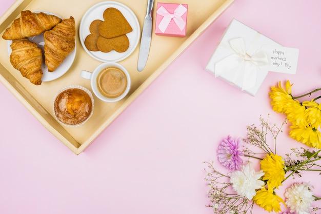 Samenstelling van bakkerij en kop op dienblad dichtbij heden en bloemen Gratis Foto