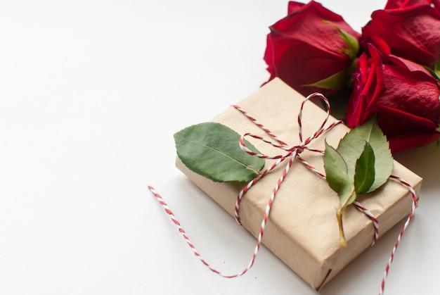 Samenstelling van cadeau en boeket van rode rozen op witte achtergrond Premium Foto