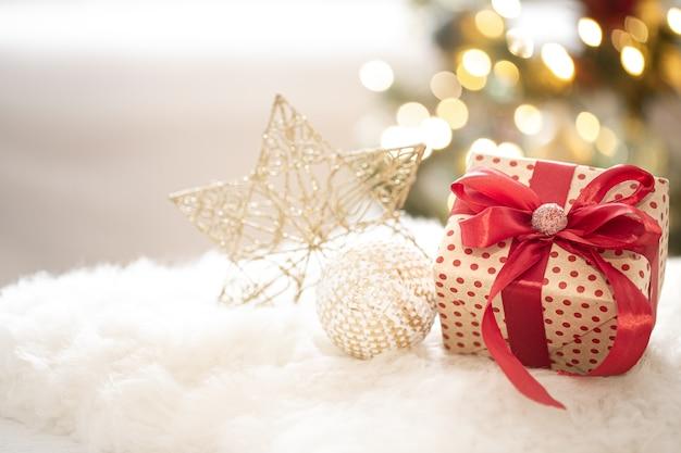 Samenstelling van een kerstcadeau en nieuwjaarsdecoratie op een lichte achtergrond met gerland-lichten. Gratis Foto