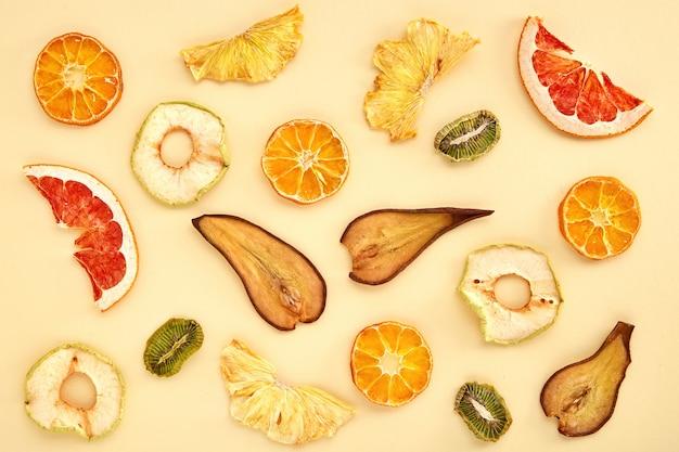 Samenstelling van gedroogde vruchten (kiwi, peer, mandarijn, sinaasappel, grapefruit, appel) op gekleurd. gedroogd fruit bovenaanzicht Premium Foto