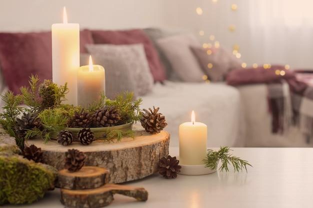 Samenstelling van kaarsen op witte tafel tegen de achtergrond van de bank thuis Premium Foto