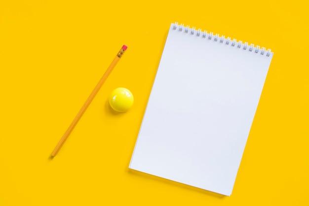 Samenstelling van notitieboekjestift en gele magneet Gratis Foto