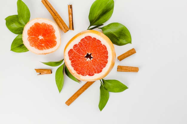 Samenstelling van plakjes grapefruit en groene bladeren in de buurt van kaneel Gratis Foto