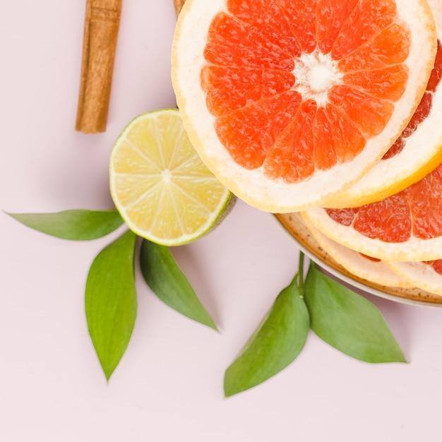 Samenstelling van plakjes grapefruit met limoen en groene bladeren in de buurt van kaneel Gratis Foto