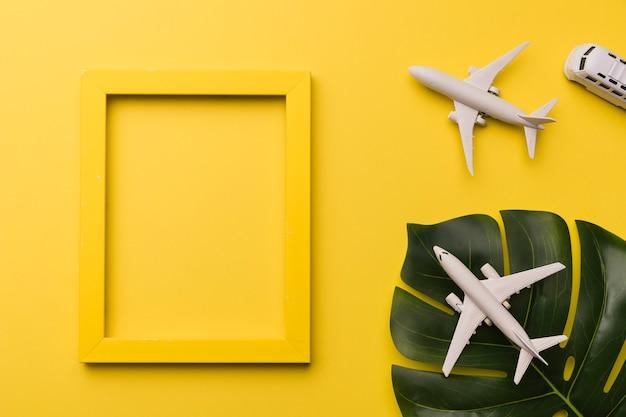 Samenstelling van speelgoed jets bus gele frame en plant blad Gratis Foto