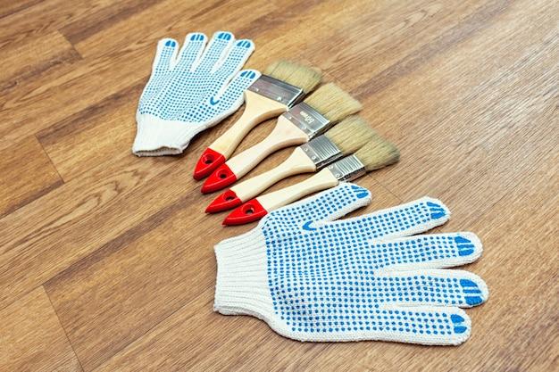 Samenstelling van tekengereedschappen met penselen, handschoenen en verfroller op de houten vloer Premium Foto