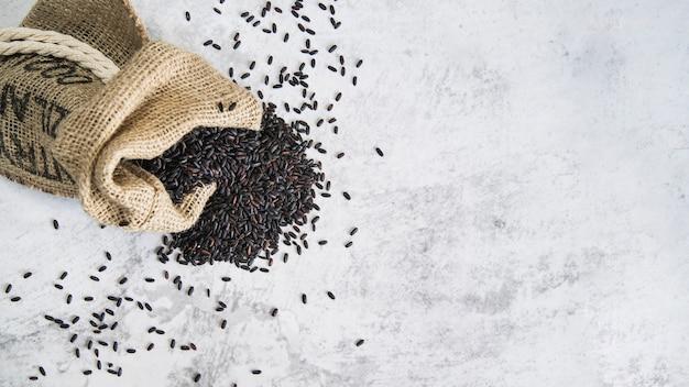Samenstelling van verspreide zwarte rijst in zak Gratis Foto
