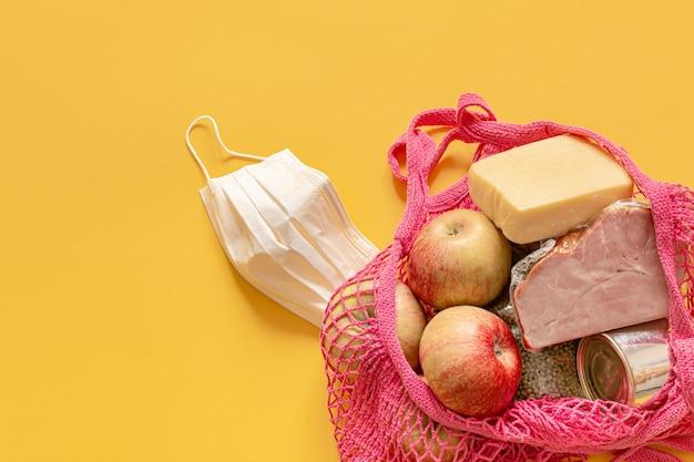 Samenstelling van voedsel in een koordzak close-up. voedselschenkingen of het concept van voedsellevering tijdens quarantaine. Gratis Foto