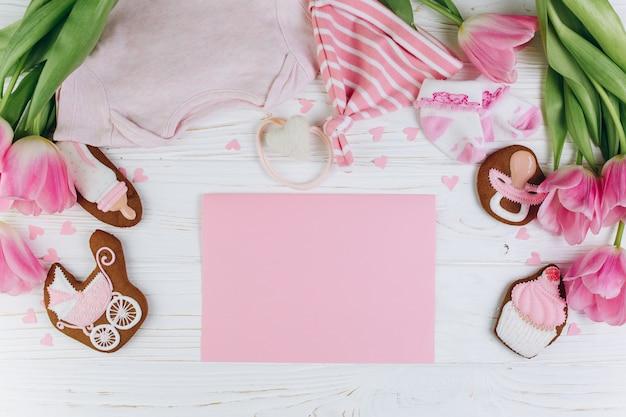 Samenstelling voor pasgeborenen op een houten achtergrond met kleding, roze tulpen en een cookies Premium Foto