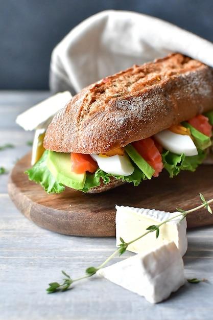 Sandwich met salami en kaas op een houten bord Premium Foto