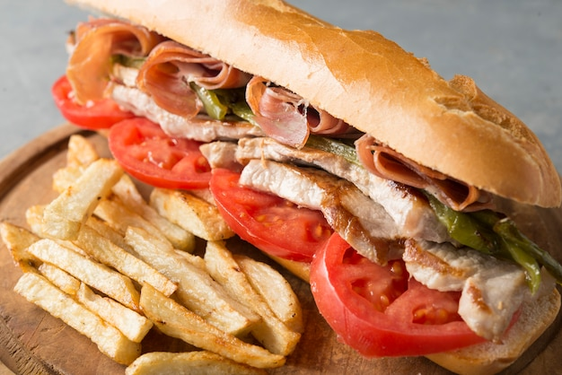Sandwich serranito typisch in andalusië met ham, gren peper en gegrilde varkenslende Premium Foto