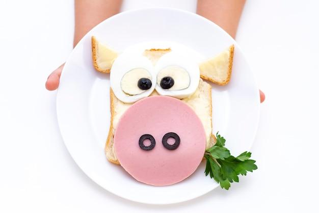 Sandwich stier. kind handen hebben een wit bord met een sandwich voor ontbijt of lunch. Premium Foto