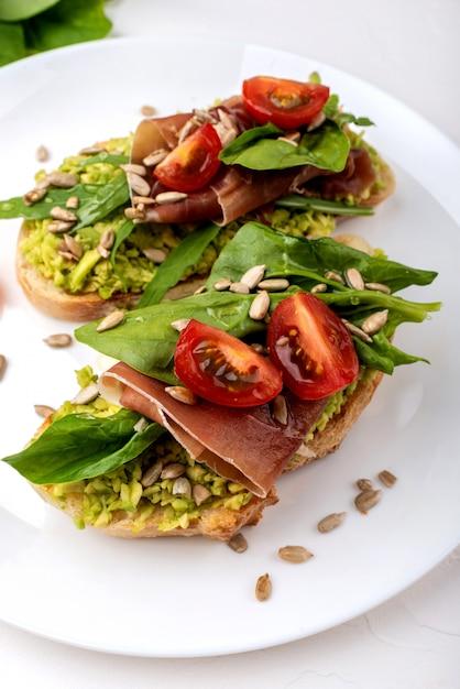 Sandwiches met avocadoroom, tomaten en jamon. Premium Foto