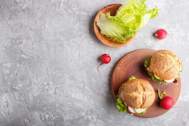 Sandwiches met kaas, radijs, sla en komkommer op een houten bord Premium Foto
