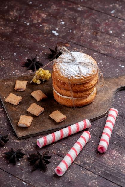 Sandwichkoekjes met room samen met stoksuikergoed op bruin bureau Gratis Foto
