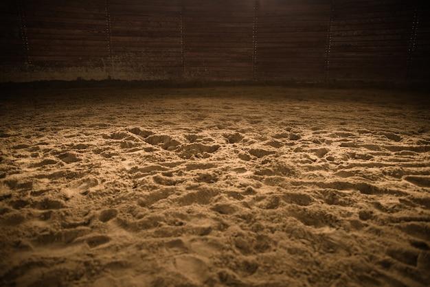 Sandy horse riding arena met lichte plek in het midden Premium Foto