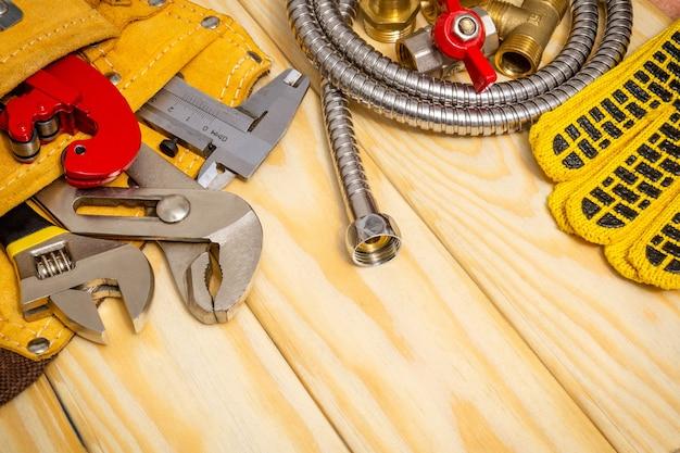 Sanitair gereedschap in de zak en slang op houten planken Premium Foto