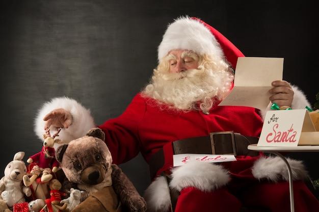 Santa claus-holdingsenvelop en het kiezen van speelgoed van grote zak Premium Foto