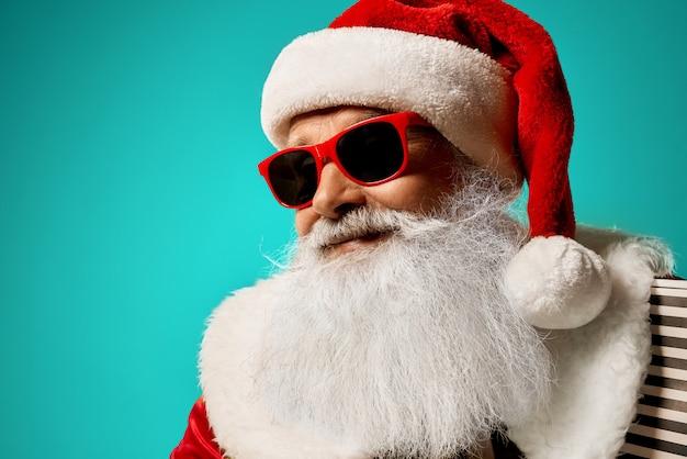 Santa claus in rode en zonnebril die glimlachen stellen Premium Foto