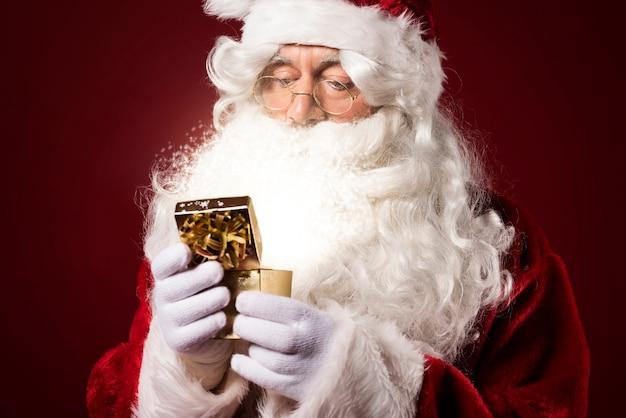Santa claus met een geschenkdoos Gratis Foto
