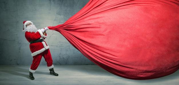 Santa claus met grote zak op lege reclamebanner met exemplaarruimte Premium Foto