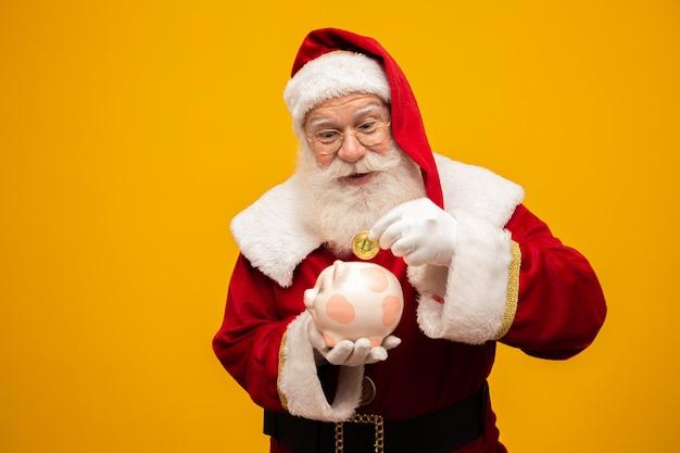 Santa claus munt ingebruikneming in een keramische spaarvarken Premium Foto