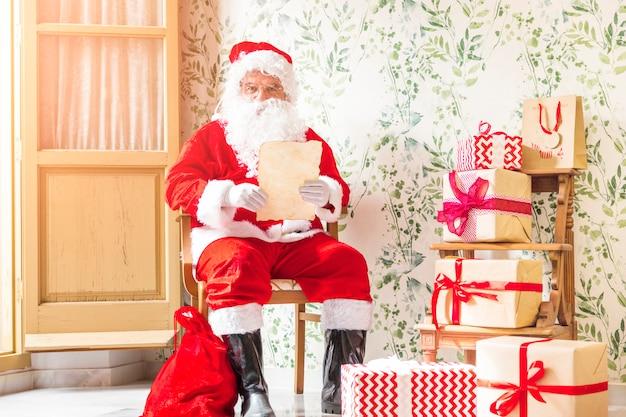 Santa claus-zitting op stoel met brief Gratis Foto