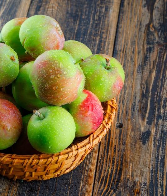Sappige appels in een rieten mand op een houten achtergrond. detailopname. Gratis Foto