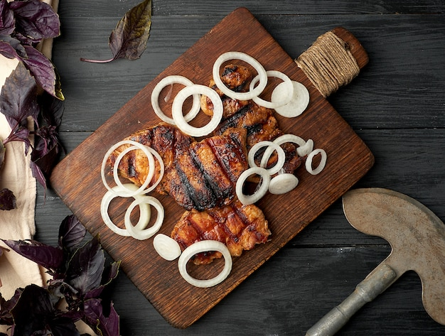 Sappige gegrilde varkenslapjes vlees op een bruine houten bord Premium Foto