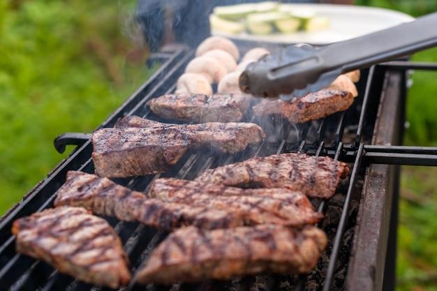 Sappige gemarmerde biefstukken en champignonhelften worden gebakken op een houtskoolgrill Premium Foto