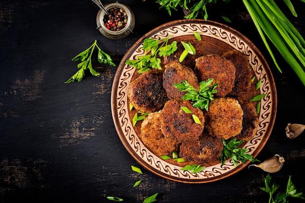 Sappige heerlijke vleeskoteletten op een donkere lijst Premium Foto
