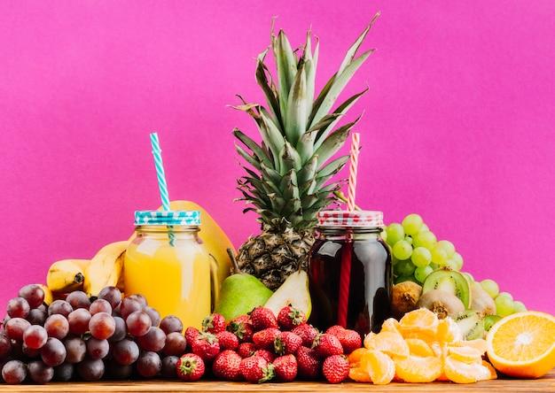 Sappige kleurrijke vruchten en sap metselaarkruiken tegen roze achtergrond Gratis Foto