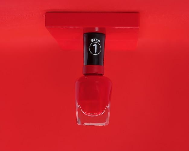 Sappige rode nagellak op een rode achtergrond zweeft hangende levitatie. het concept van handverzorging, reclame-manicuresalon, fabrikant van nagellakken, mooie nagels. close-up foto. ondertekenen stap 1 Premium Foto