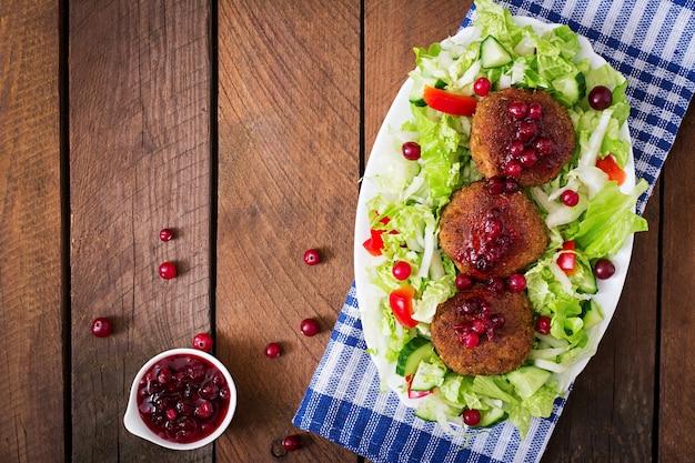 Sappige vleeskoteletten met amerikaanse veenbessaus en salade op een houten lijst in een rustieke stijl. bovenaanzicht Gratis Foto