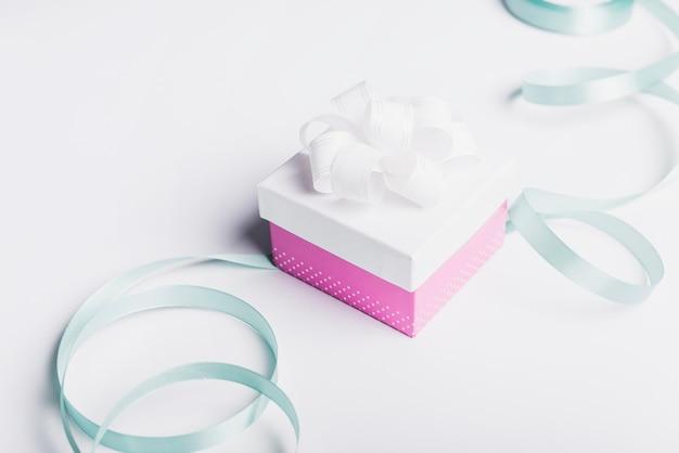 Satijnen lint met gesloten geschenkdoos op witte achtergrond Gratis Foto