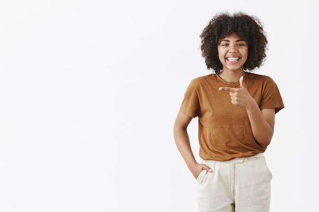 Satsified gelukkig afrikaanse amerikaanse vrouw in bruin stijlvol t-shirt en broek hand in zak glimlachend gelukkig terwijl wijzend naar links advies geven waar te gaan of welke kant kiezen boven grijze muur Gratis Foto