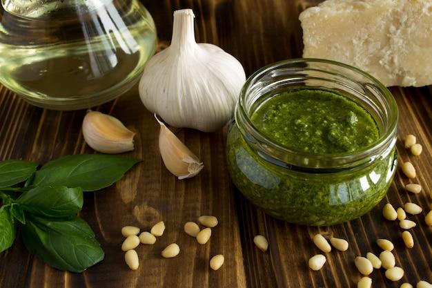 Saus pesto in de glazen pot en ingrediënten op het bruine houten oppervlak Premium Foto
