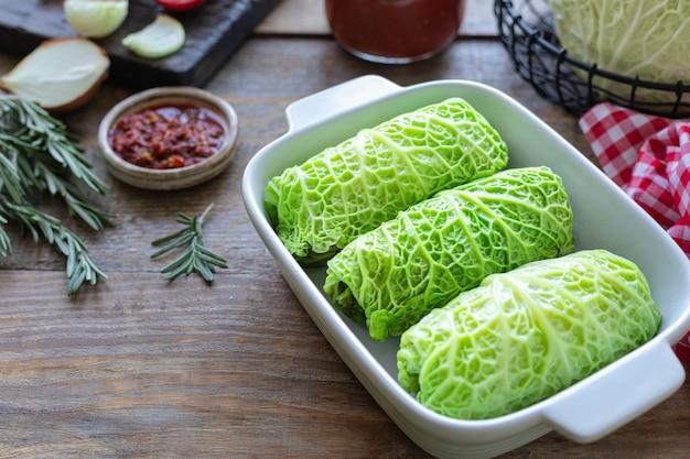Savooiekoolbroodjes die met vlees, rijst en groenten op een rustieke lijst worden gevuld Premium Foto