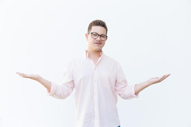Sceptische man in brillen schouderophalend Gratis Foto