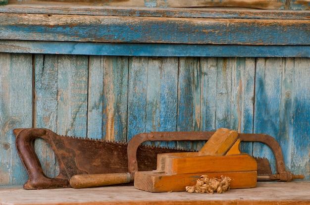 Schaafmachine, ijzerzaag en een zaag op een oude houten tafel, chips Premium Foto