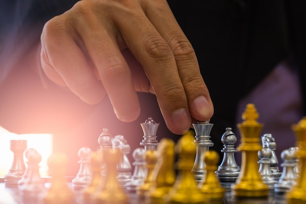 Schaakspel op schaakbord achter zakenman achtergrond. Premium Foto