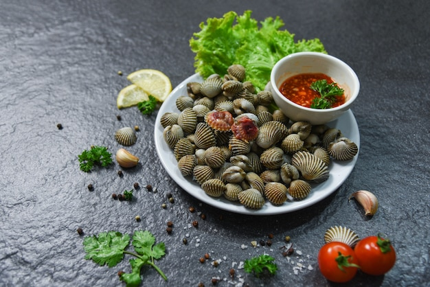 Schaaldieren zeevruchten plaat kokkels verse rauwe oceaan gourmetdiner met kruiden en specerijen Premium Foto