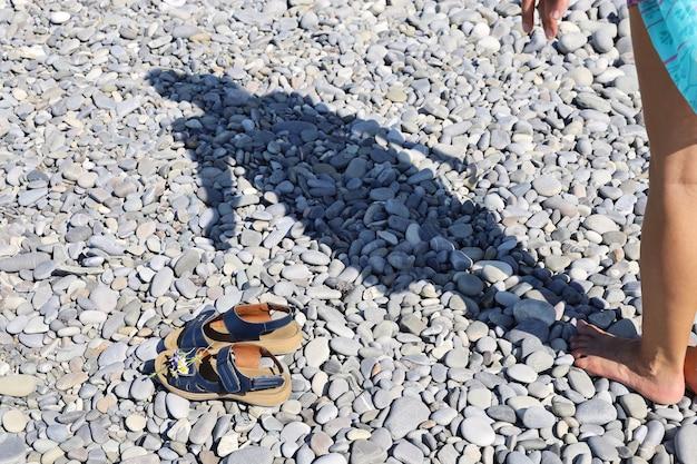 Schaduw van vrouw op kiezelstrand en sandalen op het oppervlak op de voorgrond Premium Foto