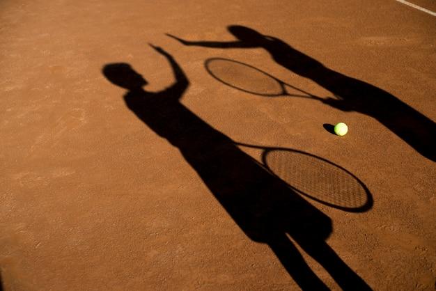 Schaduwen van twee tennissers hoog fiving Gratis Foto