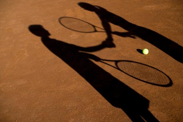 Schaduwen van twee tennisspelers Gratis Foto